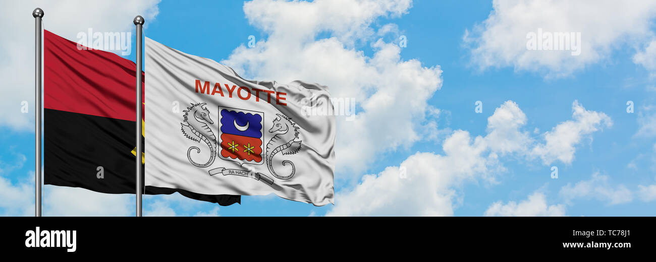 Angola and Mayotte flag waving in the wind against white cloudy blue sky together. Diplomacy concept, international relations. - Stock Image