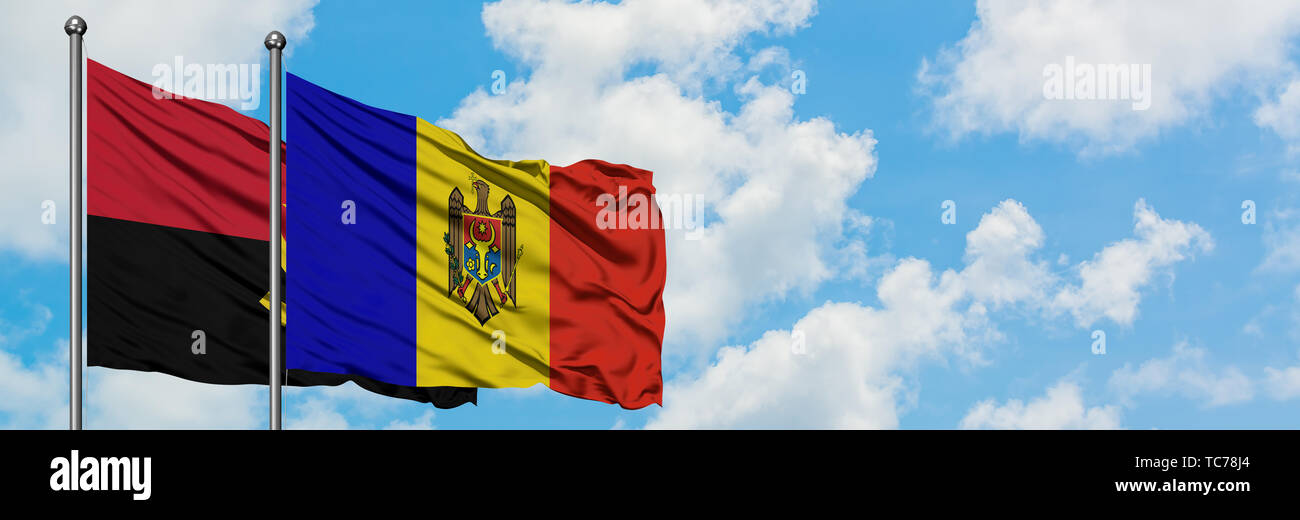 Angola and Moldova flag waving in the wind against white cloudy blue sky together. Diplomacy concept, international relations. - Stock Image