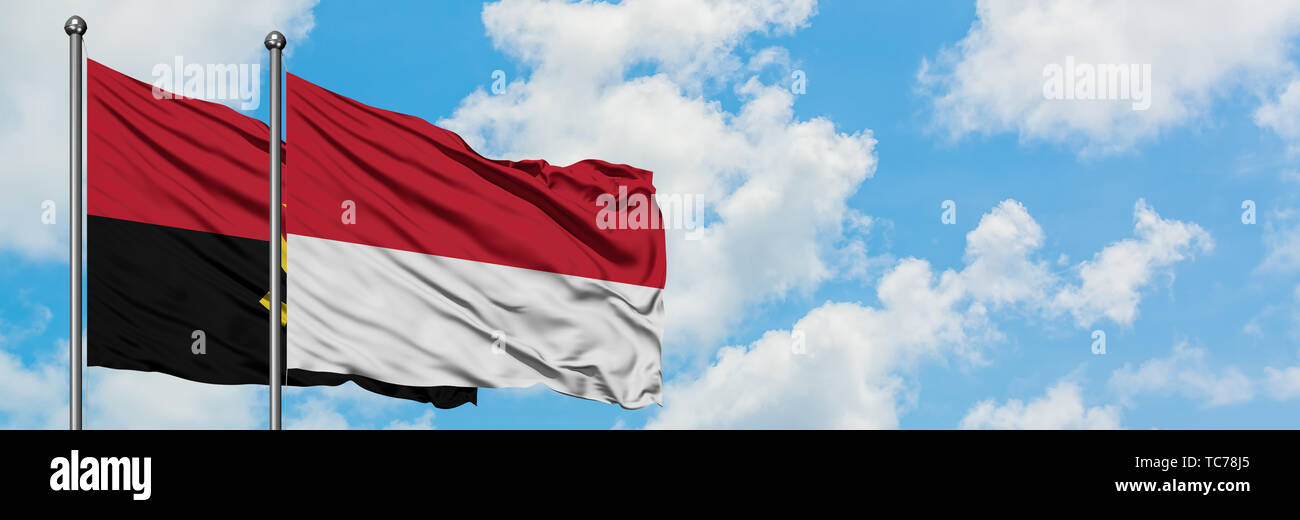 Angola and Monaco flag waving in the wind against white cloudy blue sky together. Diplomacy concept, international relations. - Stock Image