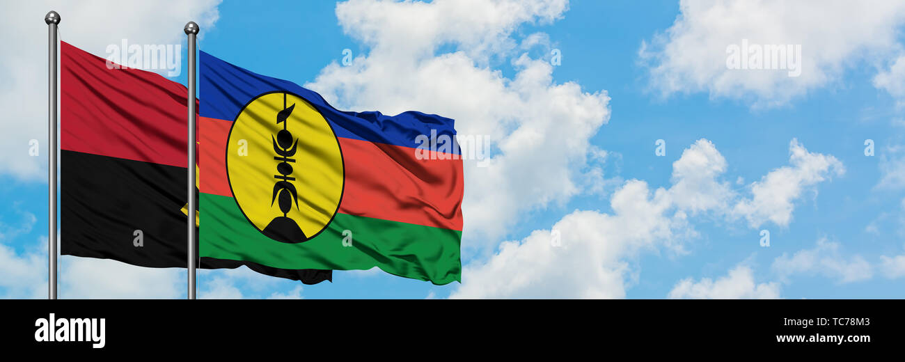 Angola and New Caledonia flag waving in the wind against white cloudy blue sky together. Diplomacy concept, international relations. - Stock Image