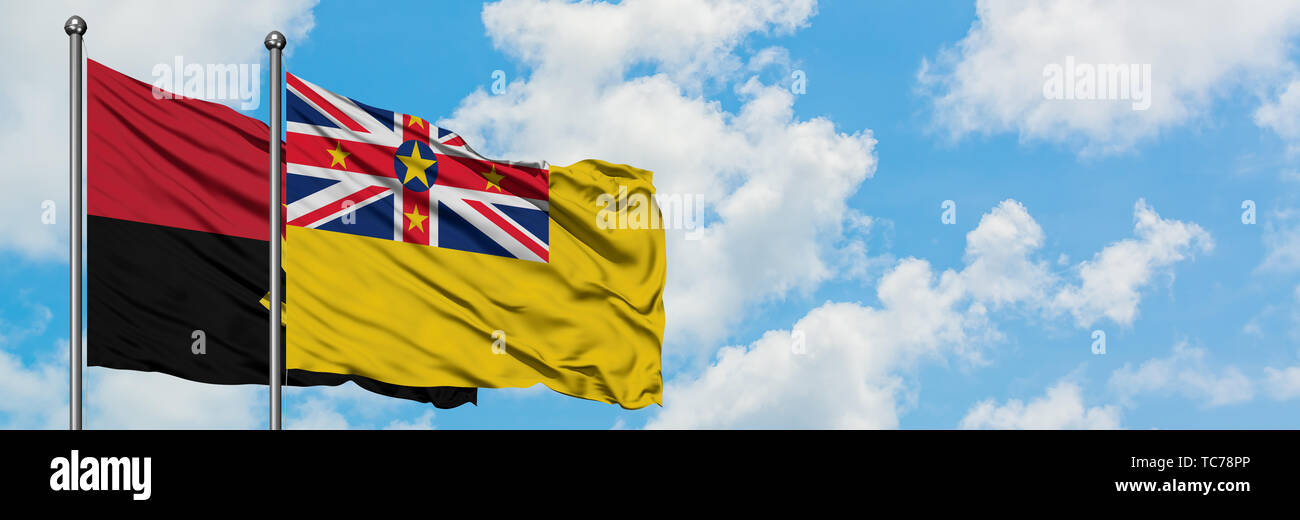 Angola and Niue flag waving in the wind against white cloudy blue sky together. Diplomacy concept, international relations. - Stock Image