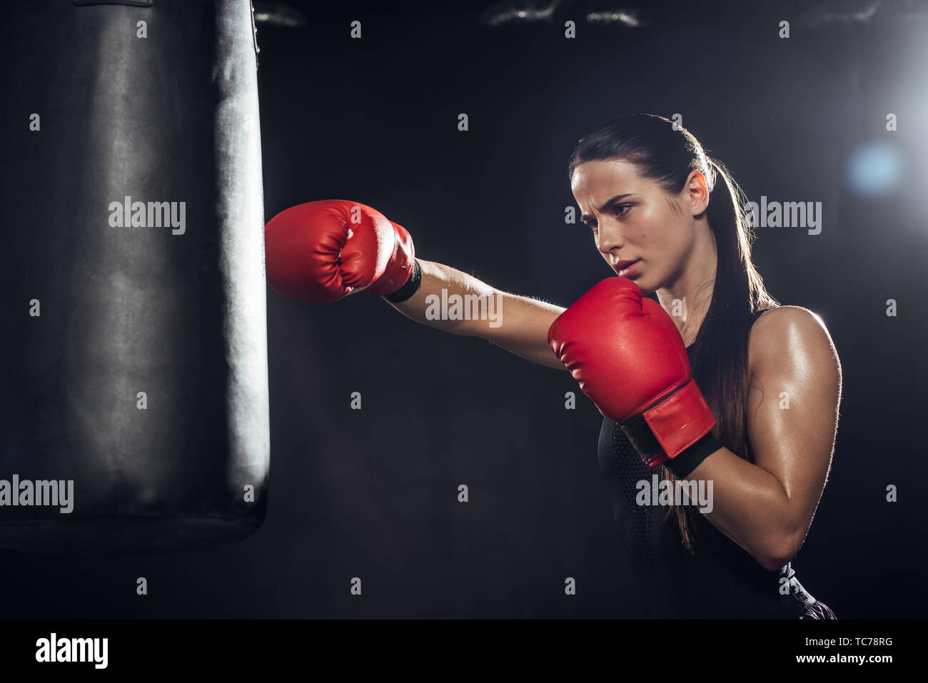 Female boxer in red boxing gloves training with punching bag on black - Stock Image