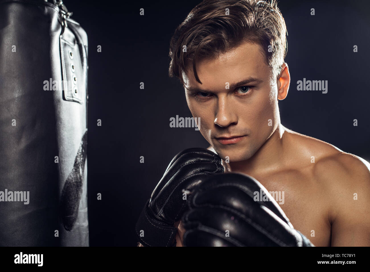Boxer standing near punching bag and looking at camera - Stock Image