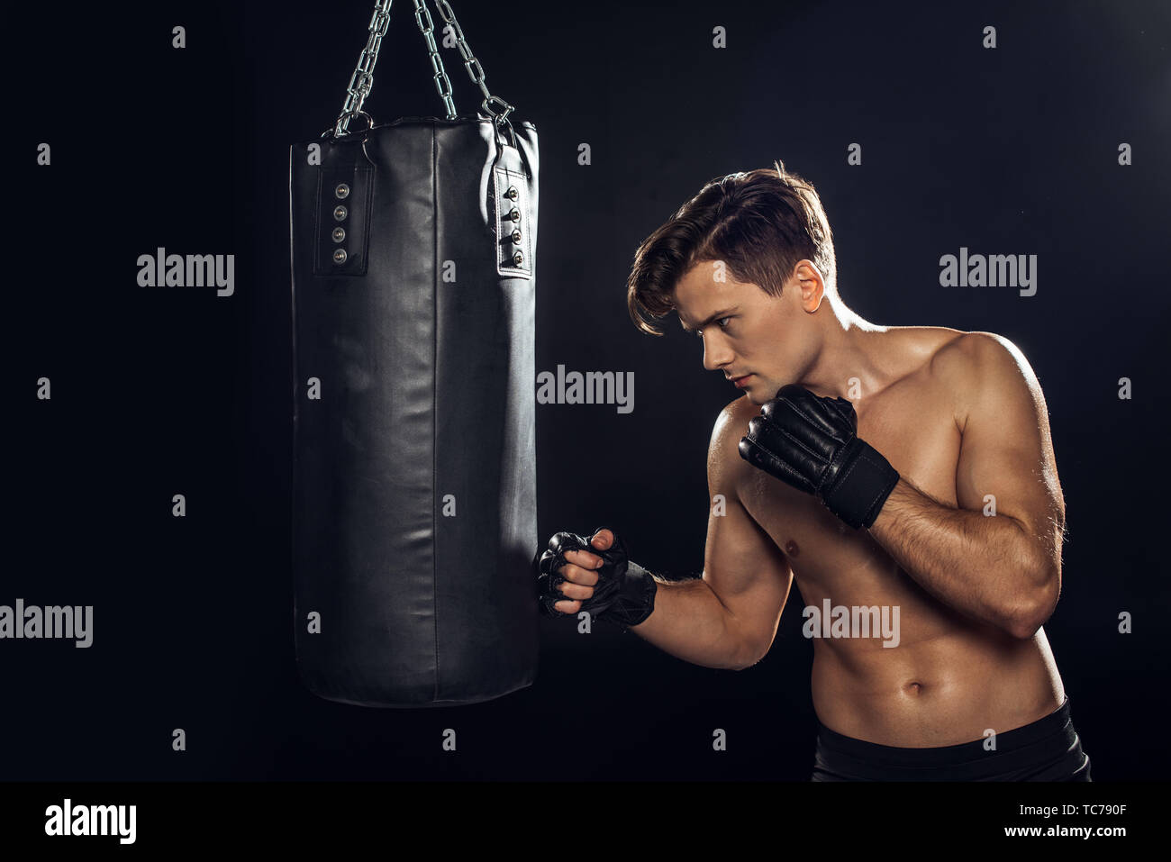 Handsome boxer in boxing gloves training with punching bag on black - Stock Image