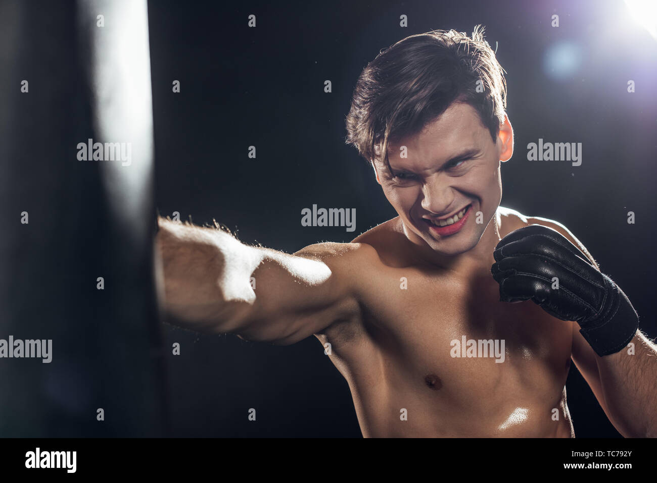 Handsome boxer in boxing glove training with punching bag on black - Stock Image