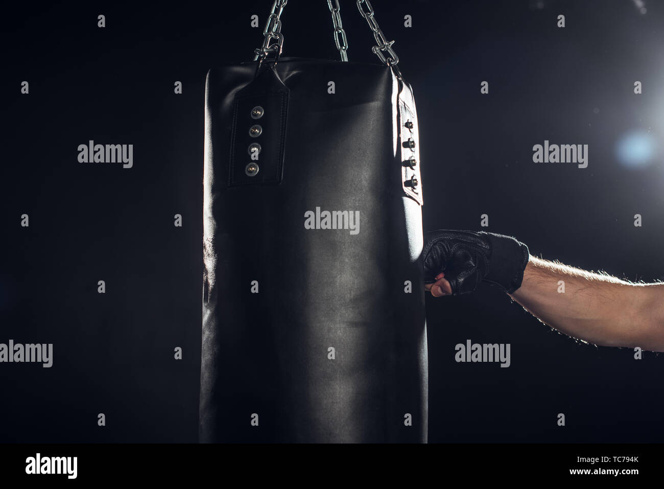 Partial view of boxer training with punching bag on black Stock Photo