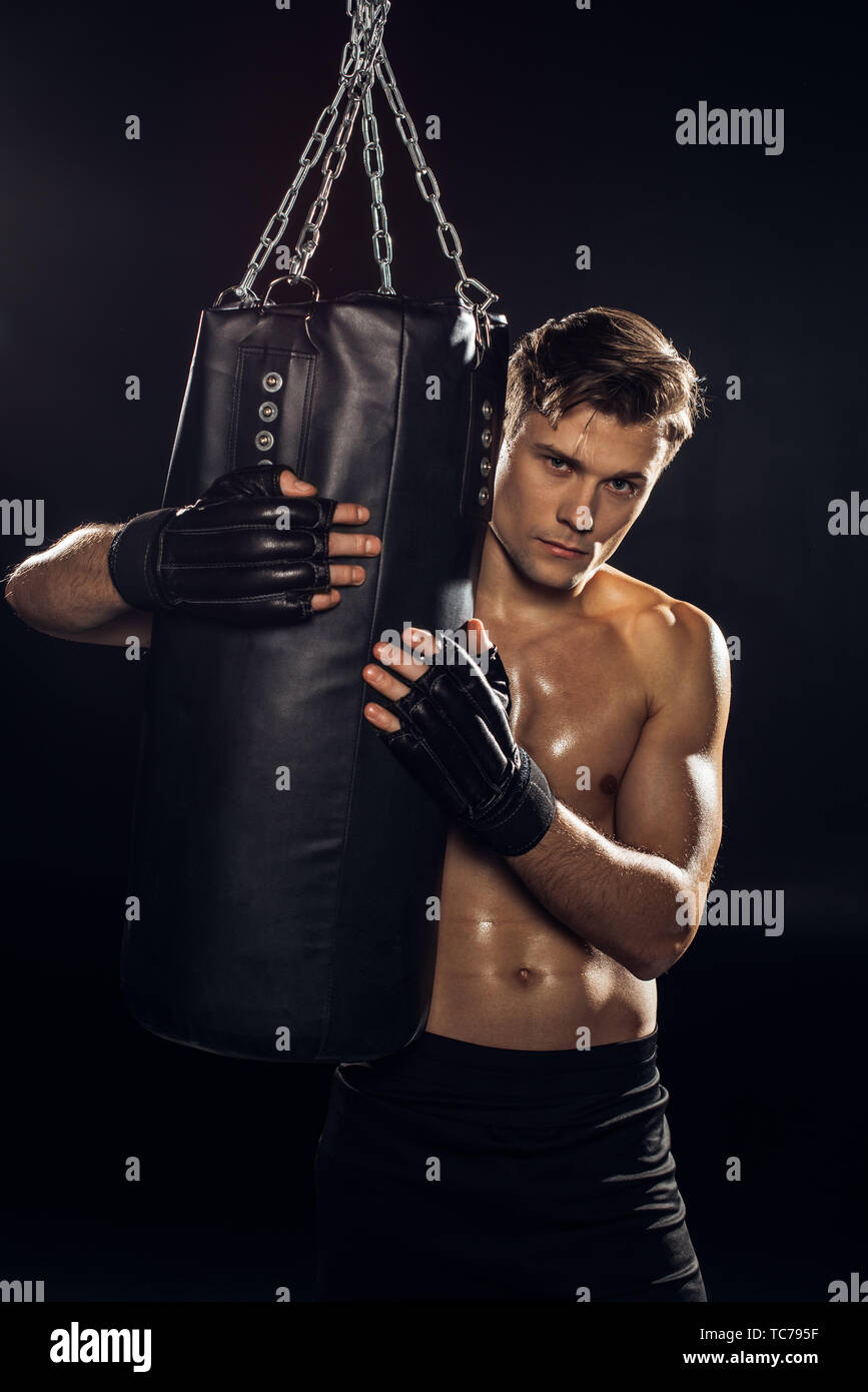 Serious boxer in gloves holding punching bag and looking at camera - Stock Image