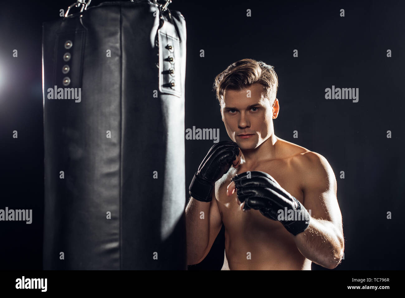 Strong boxer in gloves standing near punching bag and looking at camera - Stock Image