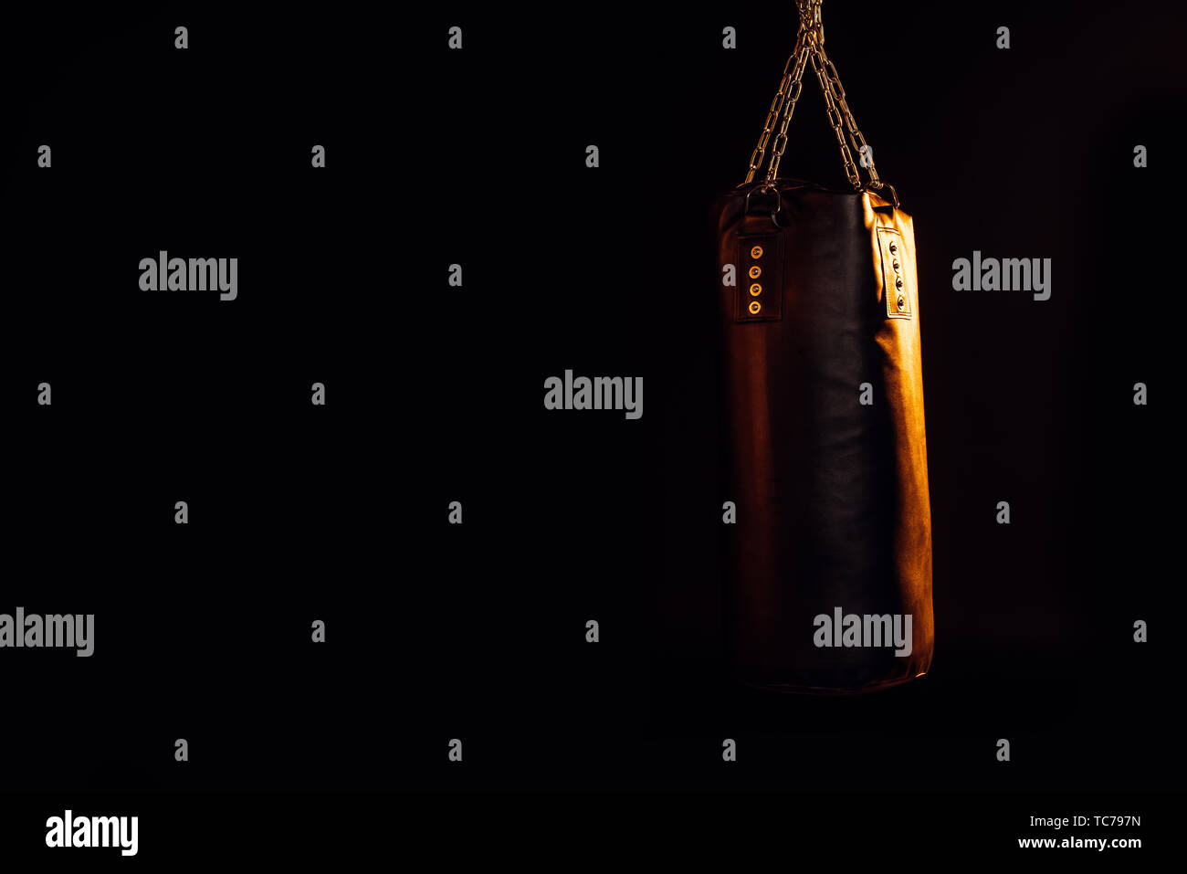Leather punching bag hanging on steel chains isolated on black - Stock Image