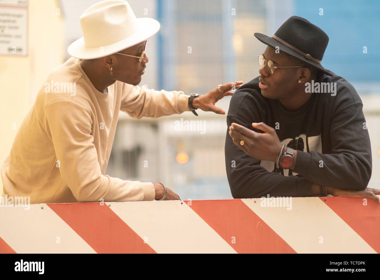 two men leaning on barrier, arguing, talking to each other, dialog, in industrial area in Munich, Germany. - Stock Image