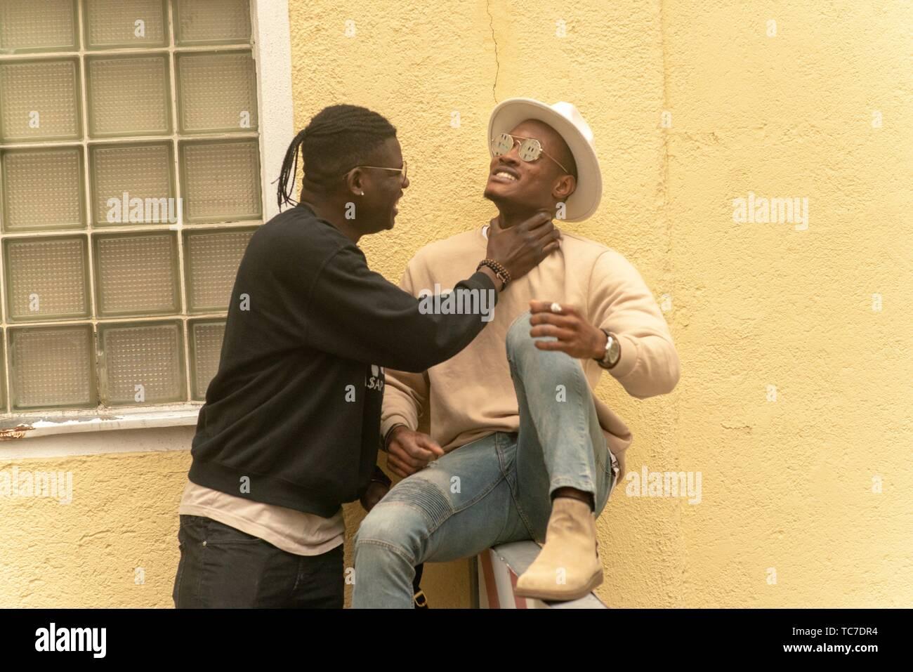 man choking friend, playing, funny, joking, Munich, Germany. - Stock Image