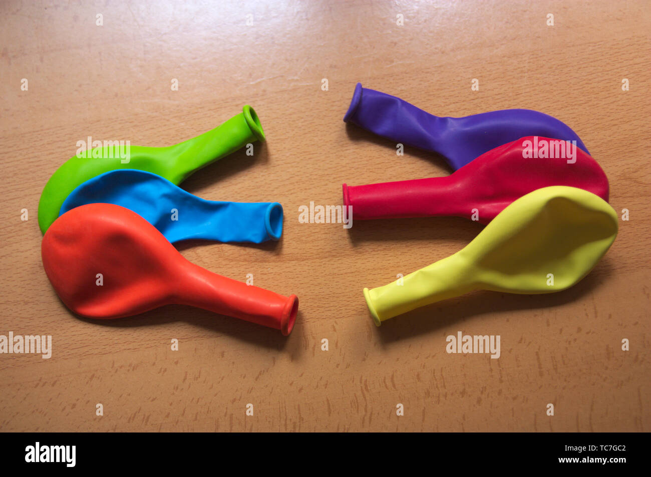 Balloons of colors red, orange, yellow, green, purple and blue on a table - Stock Image