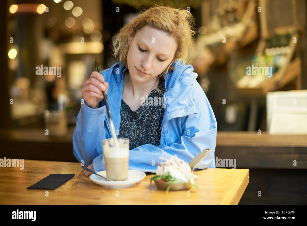 Young thoughtful woman stirring latte macchiato with drinking straw, in cafe, taking a break alone, thinking, in Munich, Germany. Stock Photo