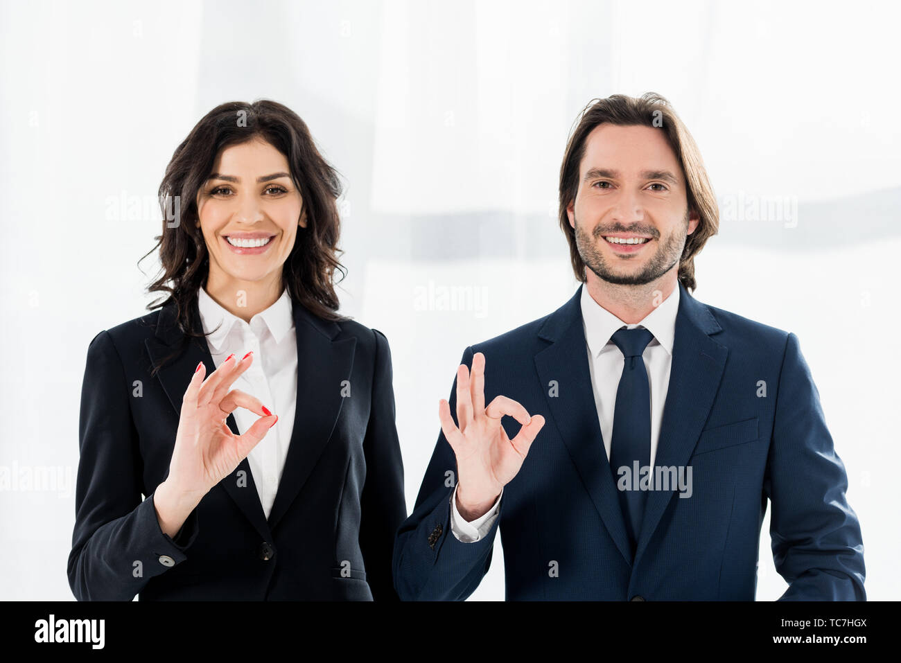 cheerful recruiters smiling while showing ok signs and looking at camera Stock Photo