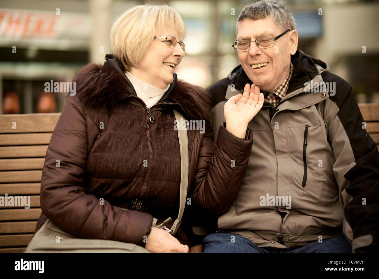 senior woman tickling senior man, jolly aged senior couple sitting on bench, enjoying togetherness, happiness, in Cottbus, Brandenburg, Germany. - Stock Image