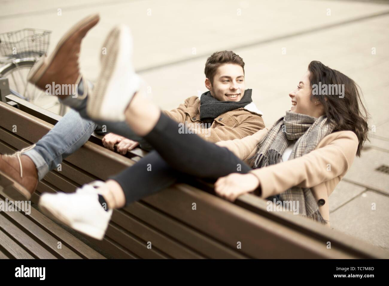 young smiling teenage couple sitting on bench the wrong way round in city, hanging out together, legs up, upside down, in Cottbus, Brandenburg, Stock Photo