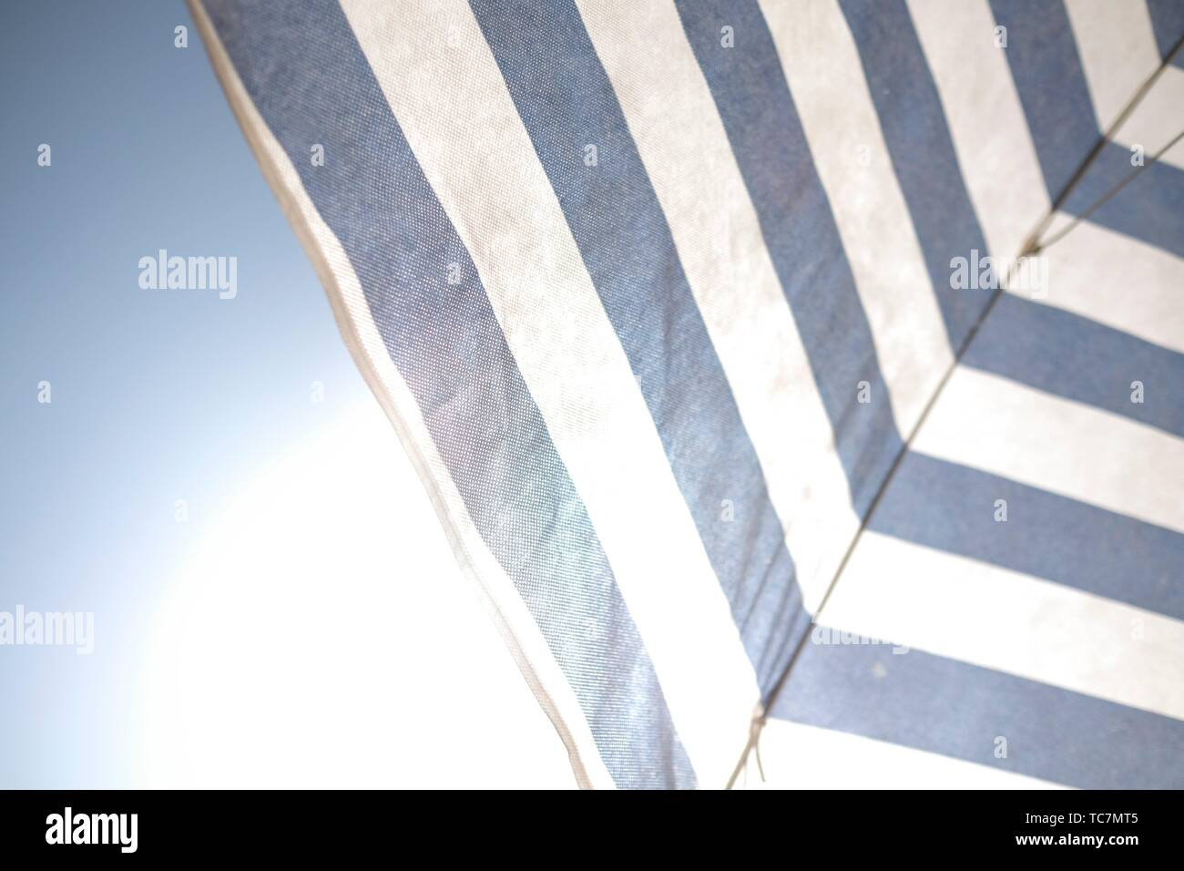 White and blue umbrella under the sun and blu sky Stock Photo