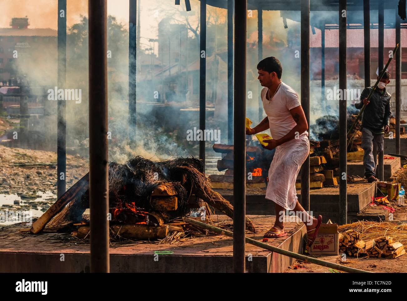 Funeral pyres are tended for many hours until cremated corpses are turned to ash, Pashupatinath Temple, a Hindu temple along the Bagmati River in - Stock Image