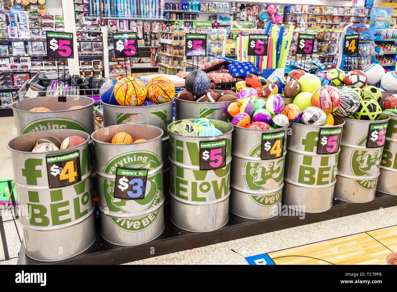 Miami Florida Five Below discount variety store inside shopping display sale inside toys balls metal barrels inexpensive cheap goods - Stock Image