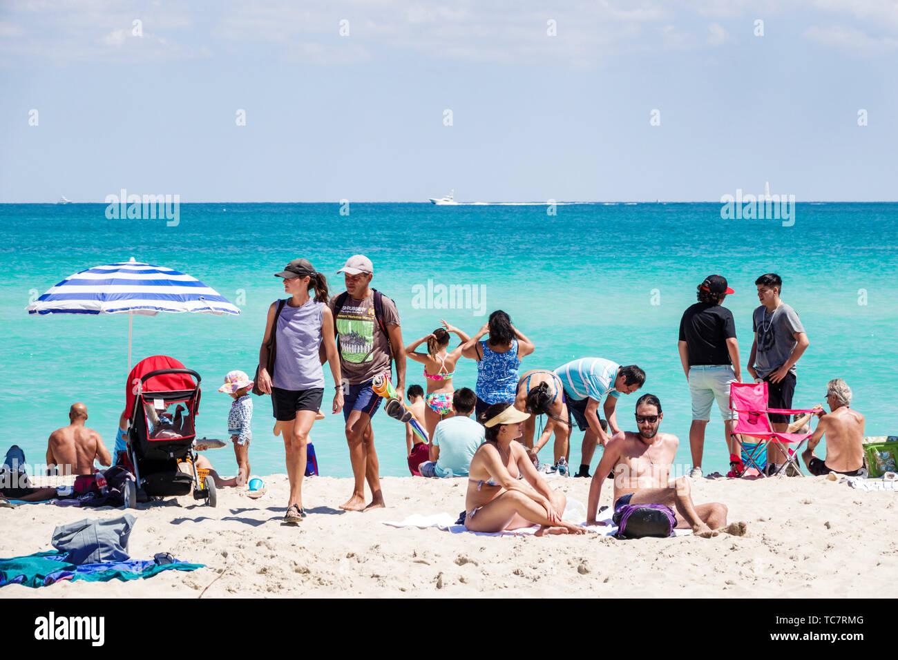 Miami Beach Florida North Beach Atlantic Ocean sunbathers Hispanic man woman couple families public water - Stock Image