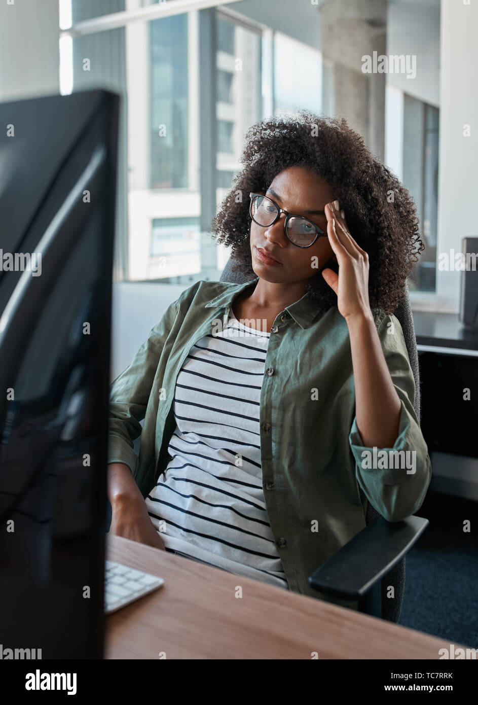 Tired overworked businesswoman looking at computer in an office - Stock Image