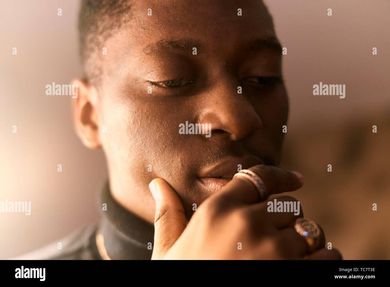 thoughtful young man, hand fondling lips, in Munich, Germany. Stock Photo