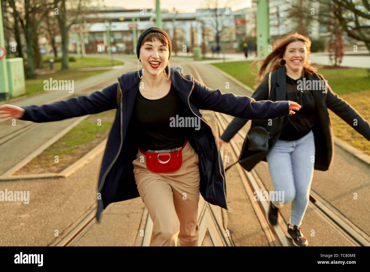 two adventurous women running at street in city Cottbus, Brandenburg, Germany. - Stock Image