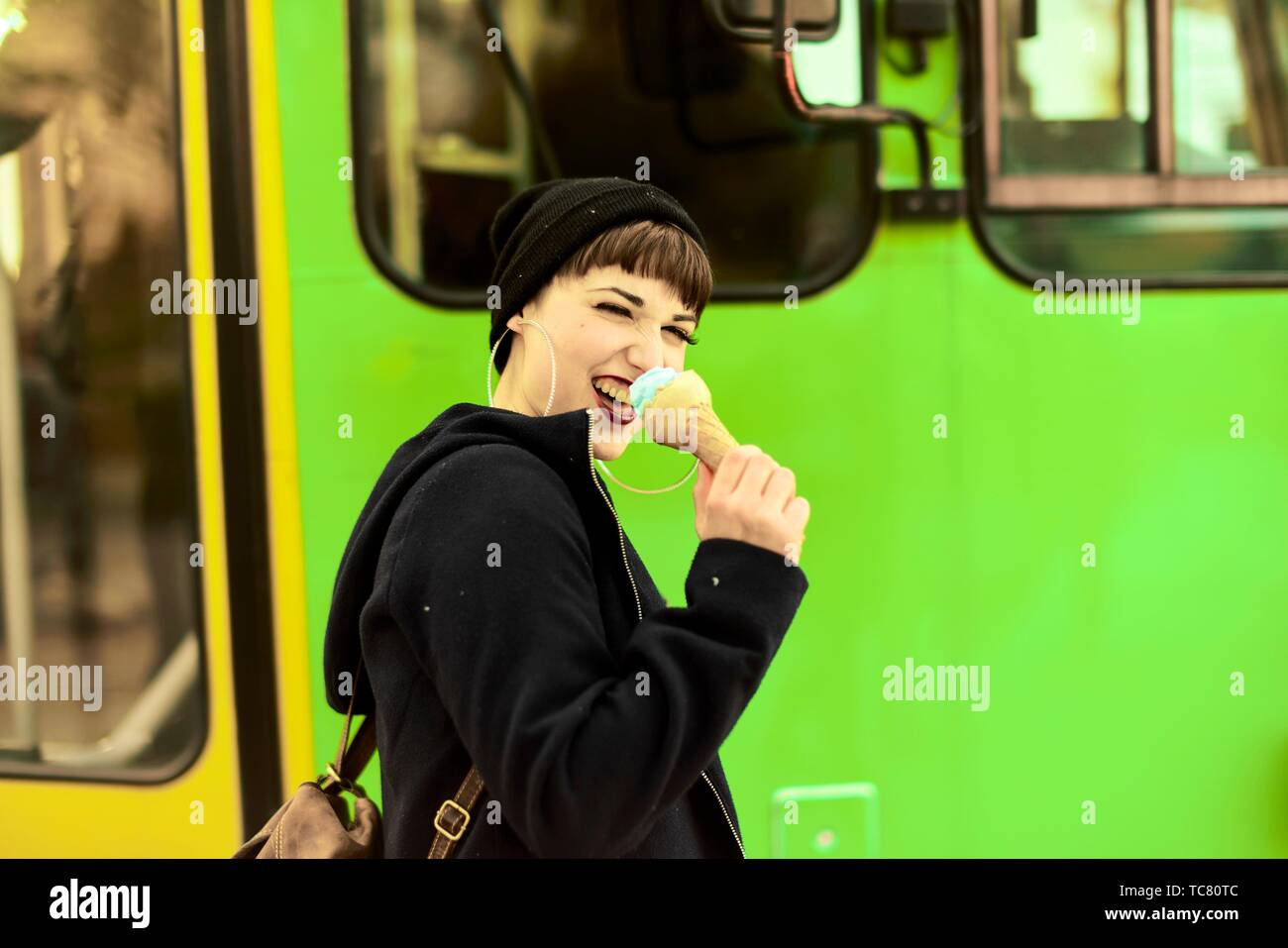 vibrant woman using ice cream cone as microphone, screaming loud her opinion, during warm winter day, in city Cottbus, Brandenburg, Germany. - Stock Image