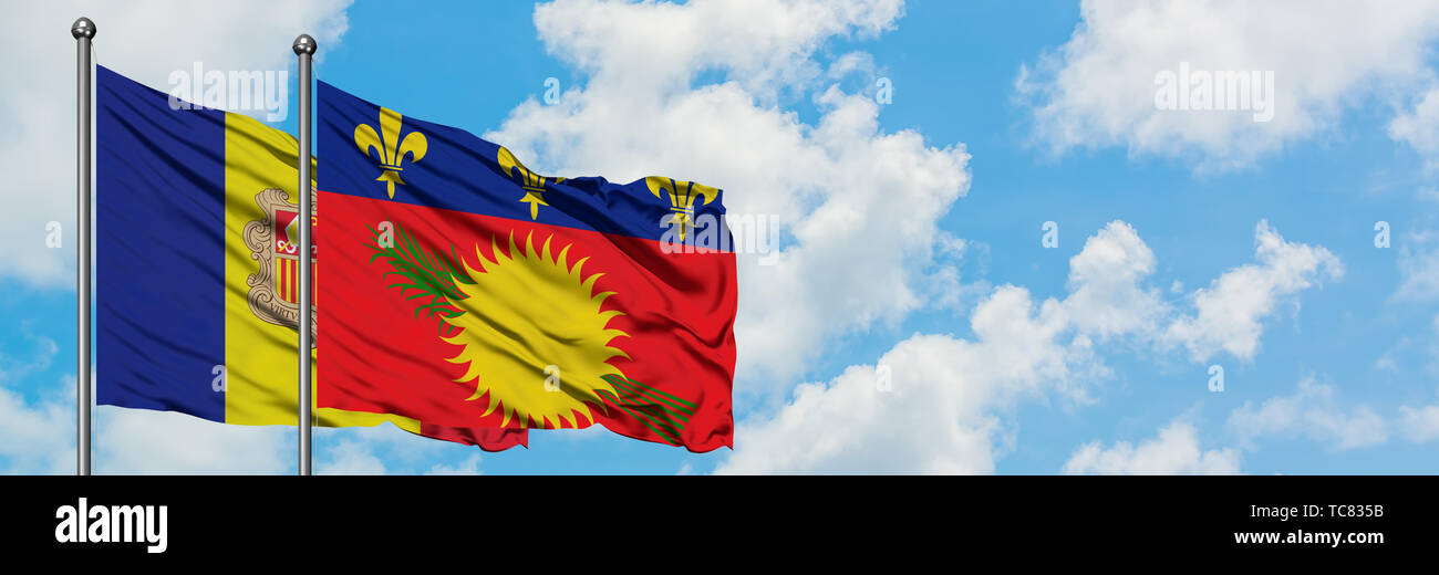 Andorra and Guadeloupe flag waving in the wind against white cloudy blue sky together. Diplomacy concept, international relations. Stock Photo
