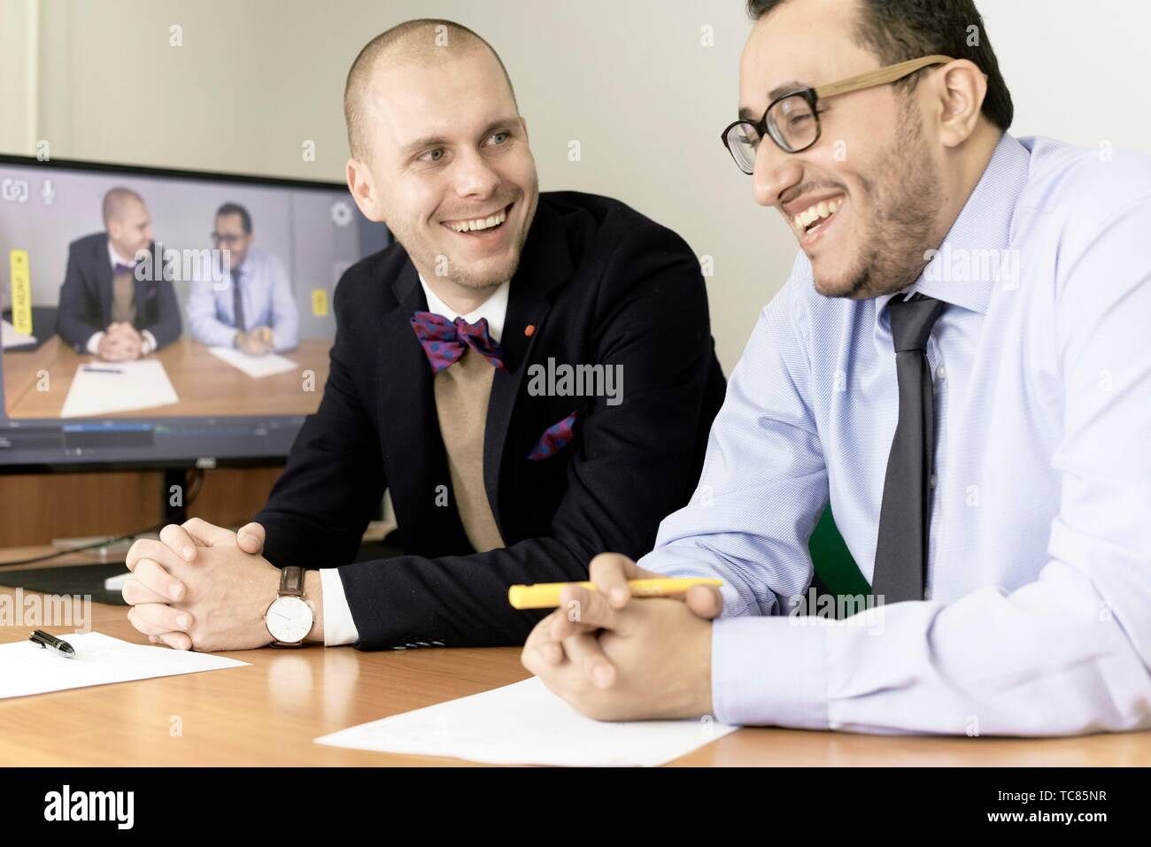 laughing business men at conference, lawyers consulting at online live stream, in office, in Cottbus, Brandenburg, Germany - Stock Image