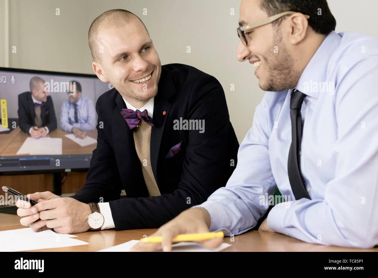 happy business men looking at each other at conference, lawyers consulting at online live stream, in Cottbus, Brandenburg, Germany - Stock Image