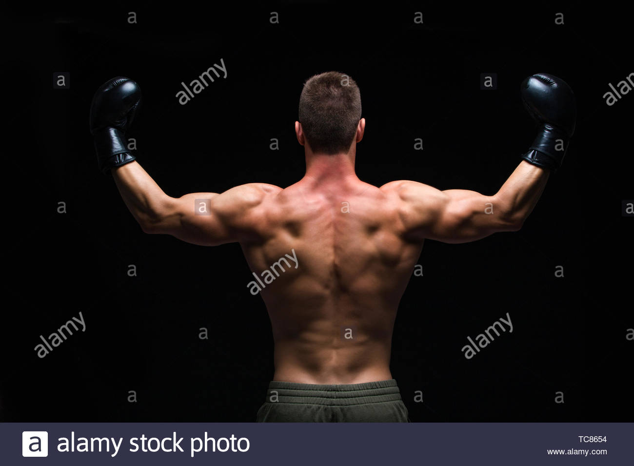 Powerful back. Muscular young man in black boxing gloves and shorts shows the different movements and strikes in the studio on a dark background - Stock Image