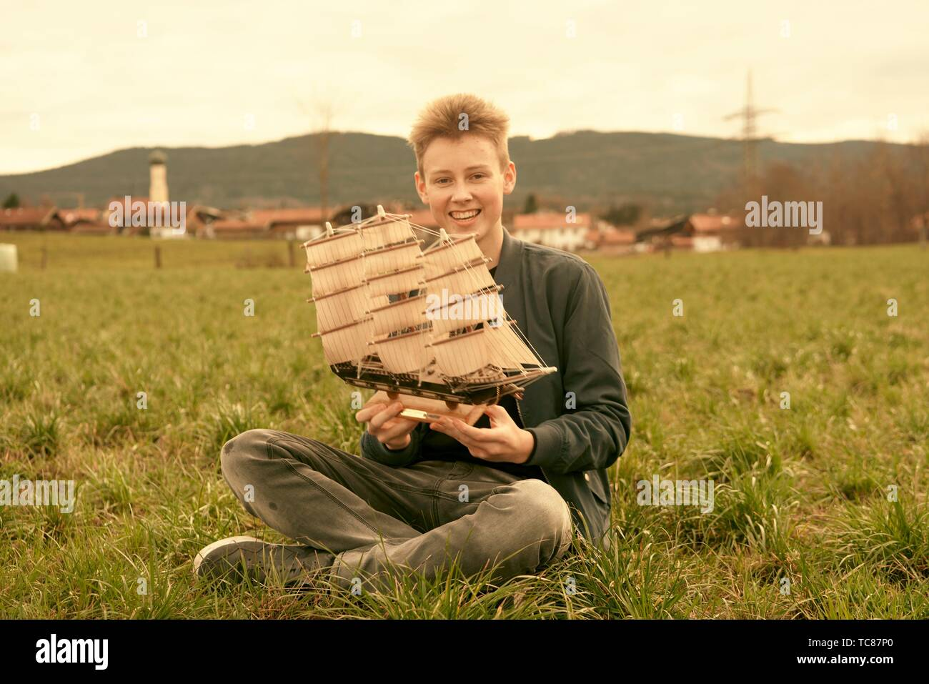 male teenager holding ship while sitting outdoors on meadow at countryside, travel lust, happy laughing, in Waakirchen, Bavaria, Germany - Stock Image