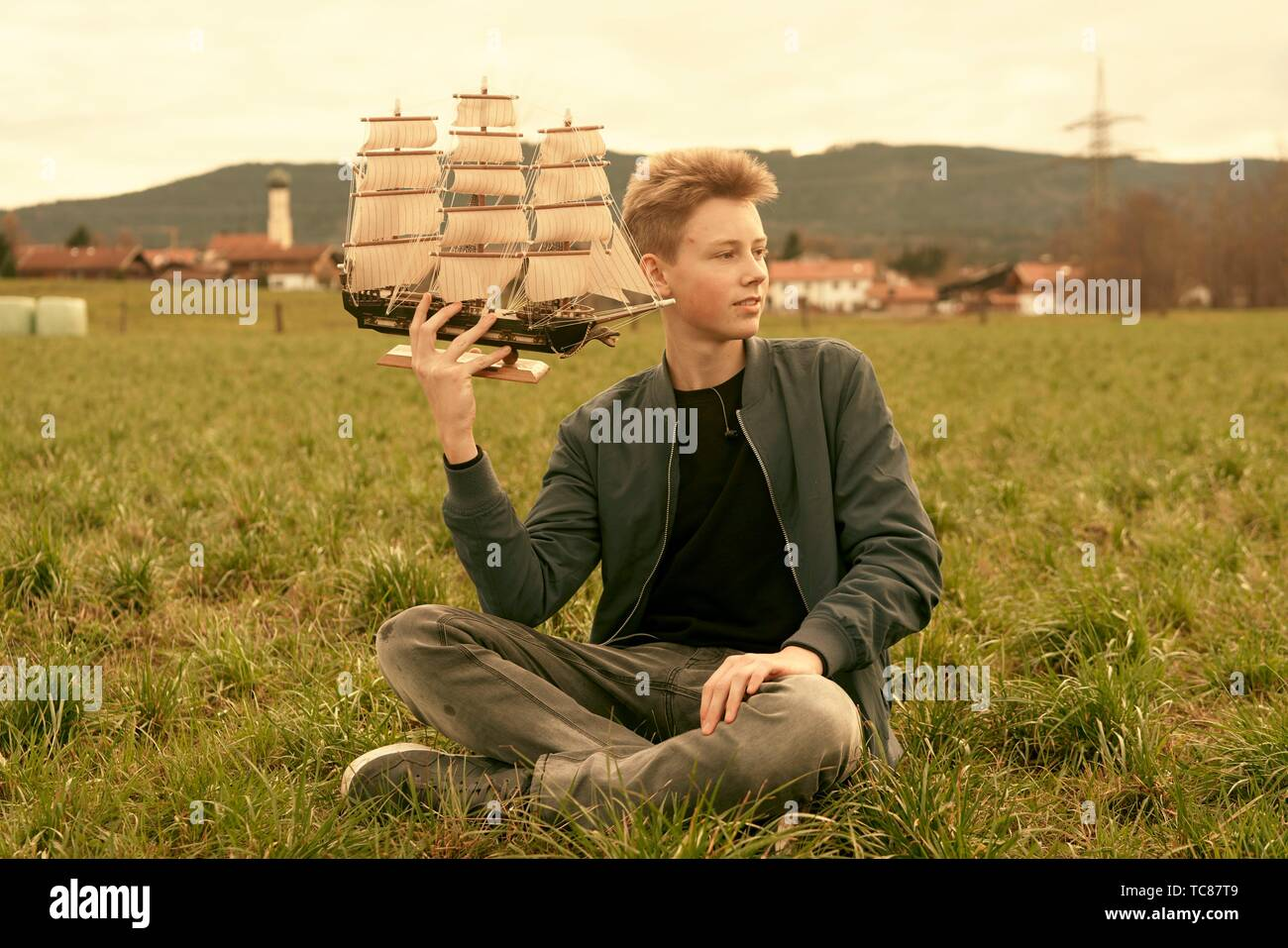 male teenager holding ship while sitting outdoors on meadow at countryside, travel lust, pensive mood, in Waakirchen, Bavaria, Germany - Stock Image