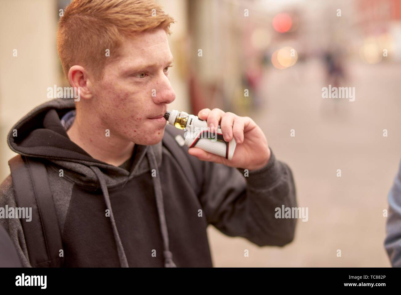 portrait of young man using electronic cigarette. - Stock Image