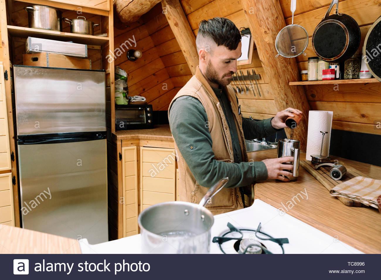 Man preparing coffee in cabin kitchen - Stock Image