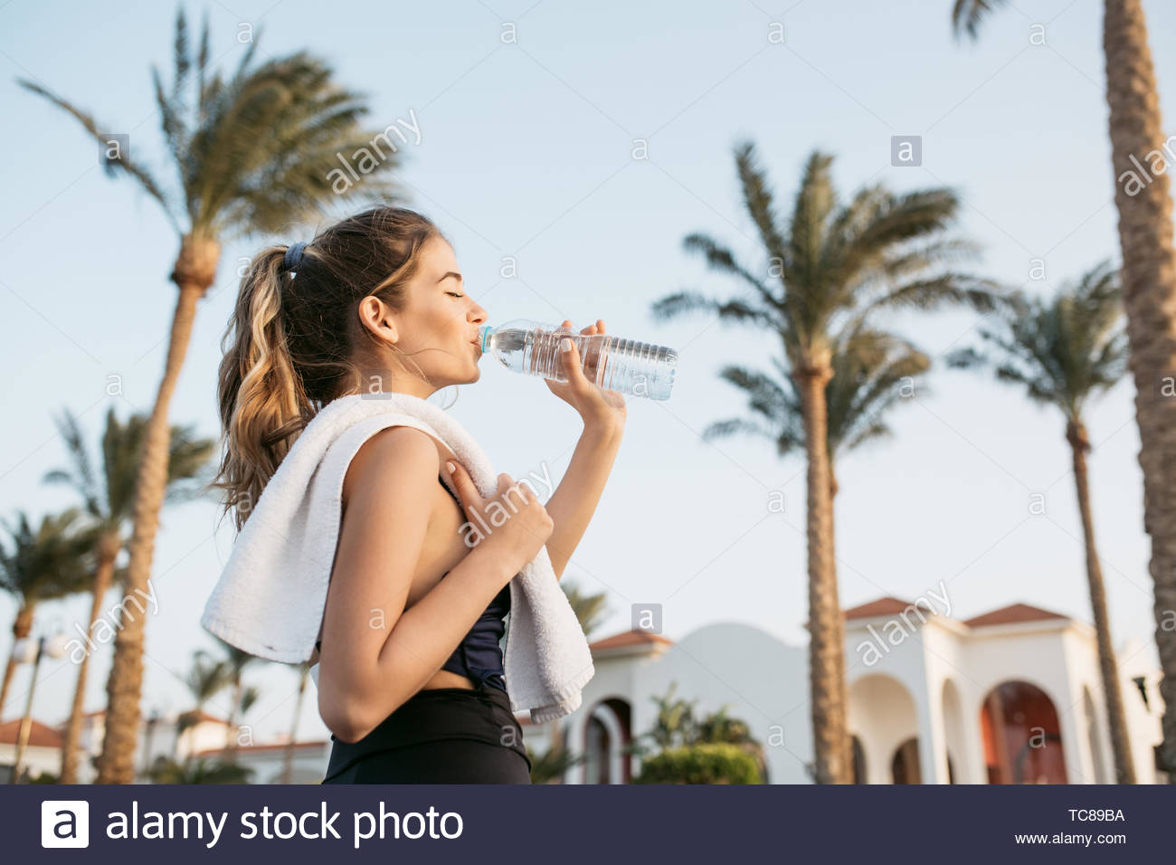 Portrait attractive young woman in sportswear drinking water from bottle on palms and sky background. Tropical city, sunny morning, relaxing with closed eyes, workout Stock Photo