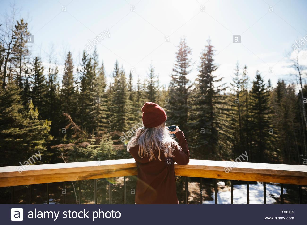 Woman drinking coffee on sunny balcony overlooking woods - Stock Image