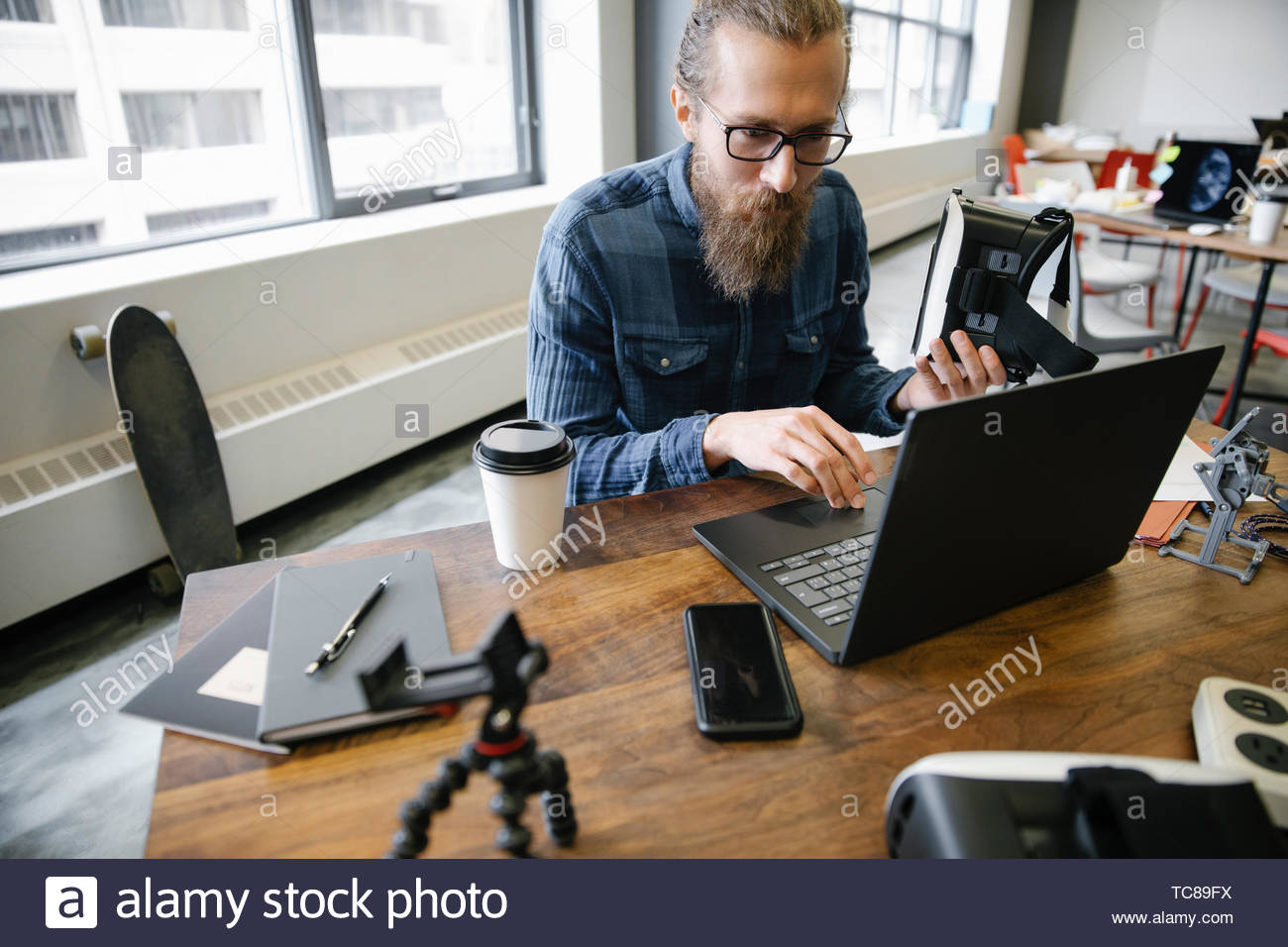 Computer programmer with virtual reality simulator glasses working at laptop in office - Stock Image