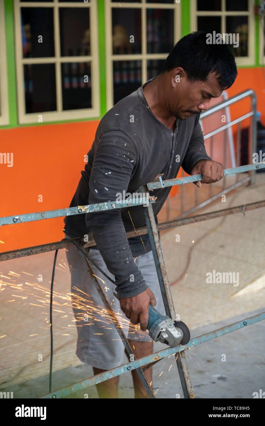 Man cutting iron bar with angle grinder at 'Vihara Qikung' Ji Gong House Of Help in Singkawang, West Kalimantan, Indonesia - Stock Image