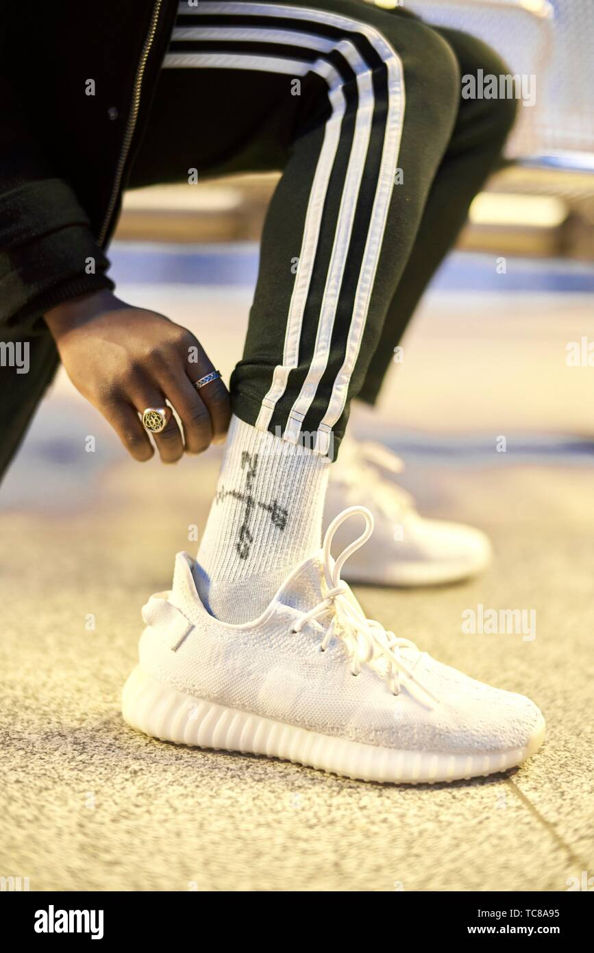 man fixing outfit, wearing white socks with compass sign, white shoes and trackies, in Munich, Germany. - Stock Image
