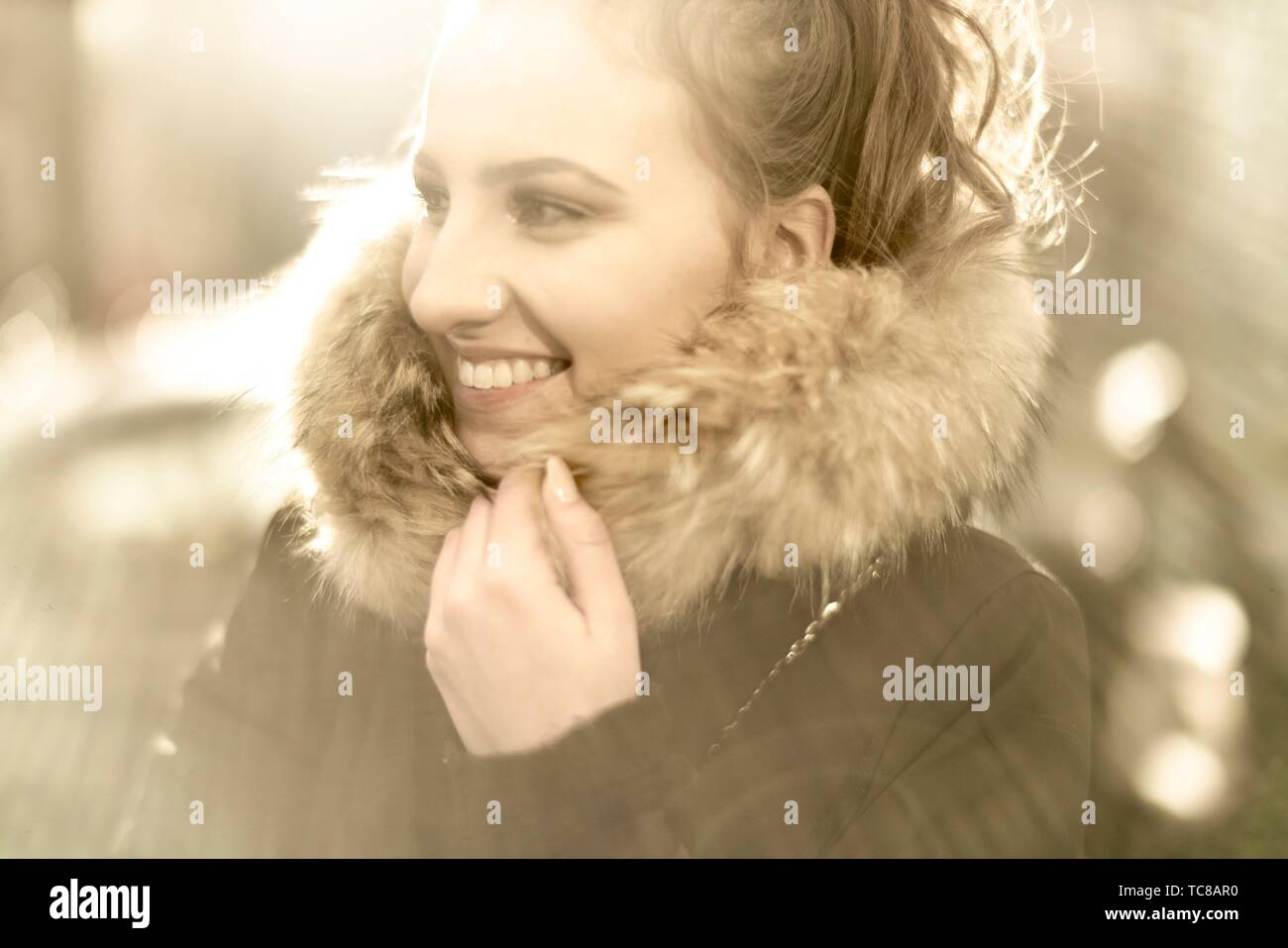 young woman wearing winter jacket with pelt collar in sunlight, in Munich, Germany. Stock Photo
