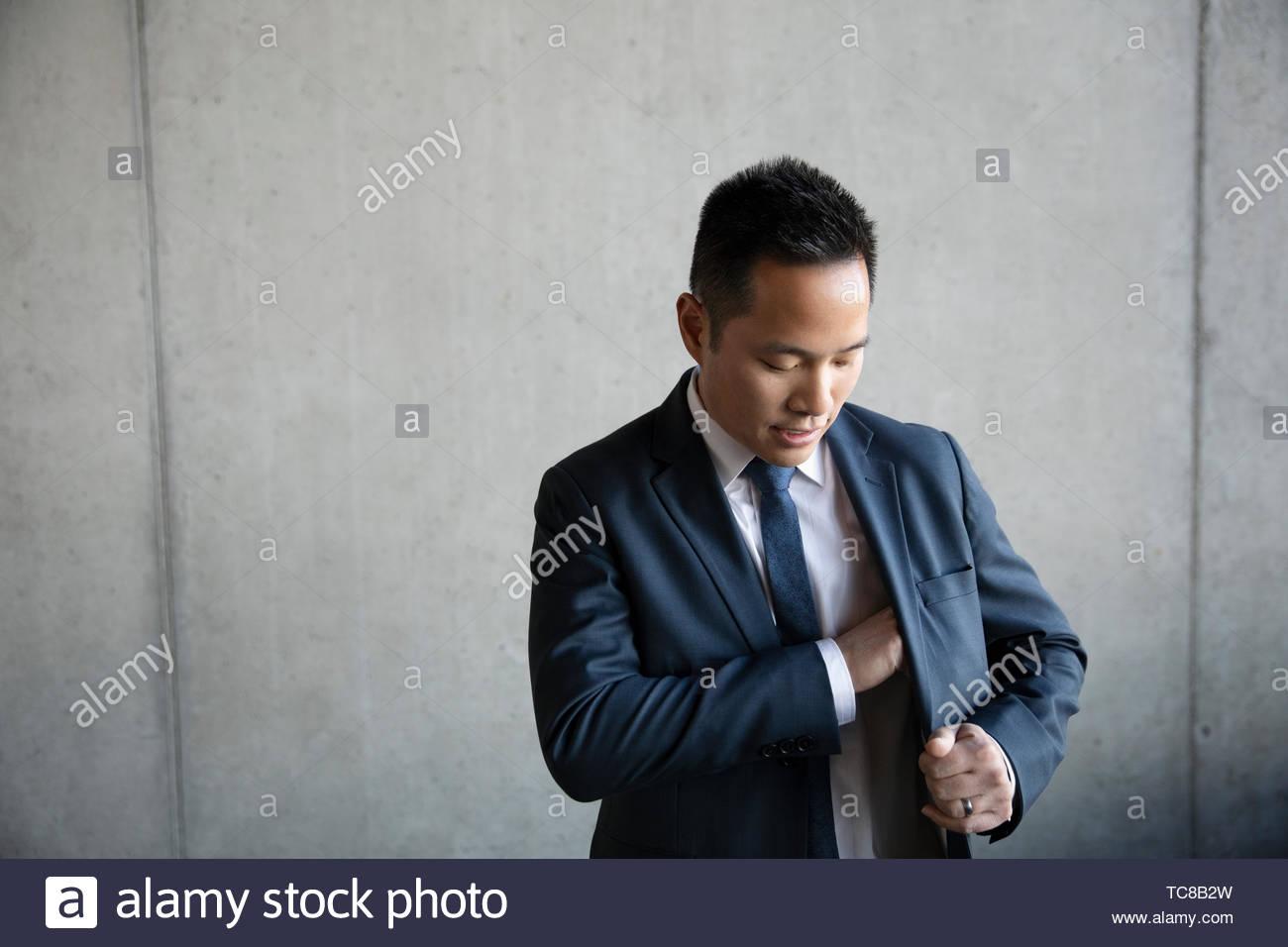 Businessman reaching inside suit jacket pocket - Stock Image