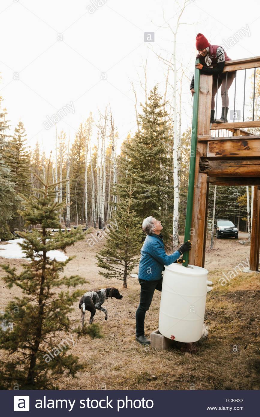 Couple with dog installing rain barrel outside cabin Stock Photo