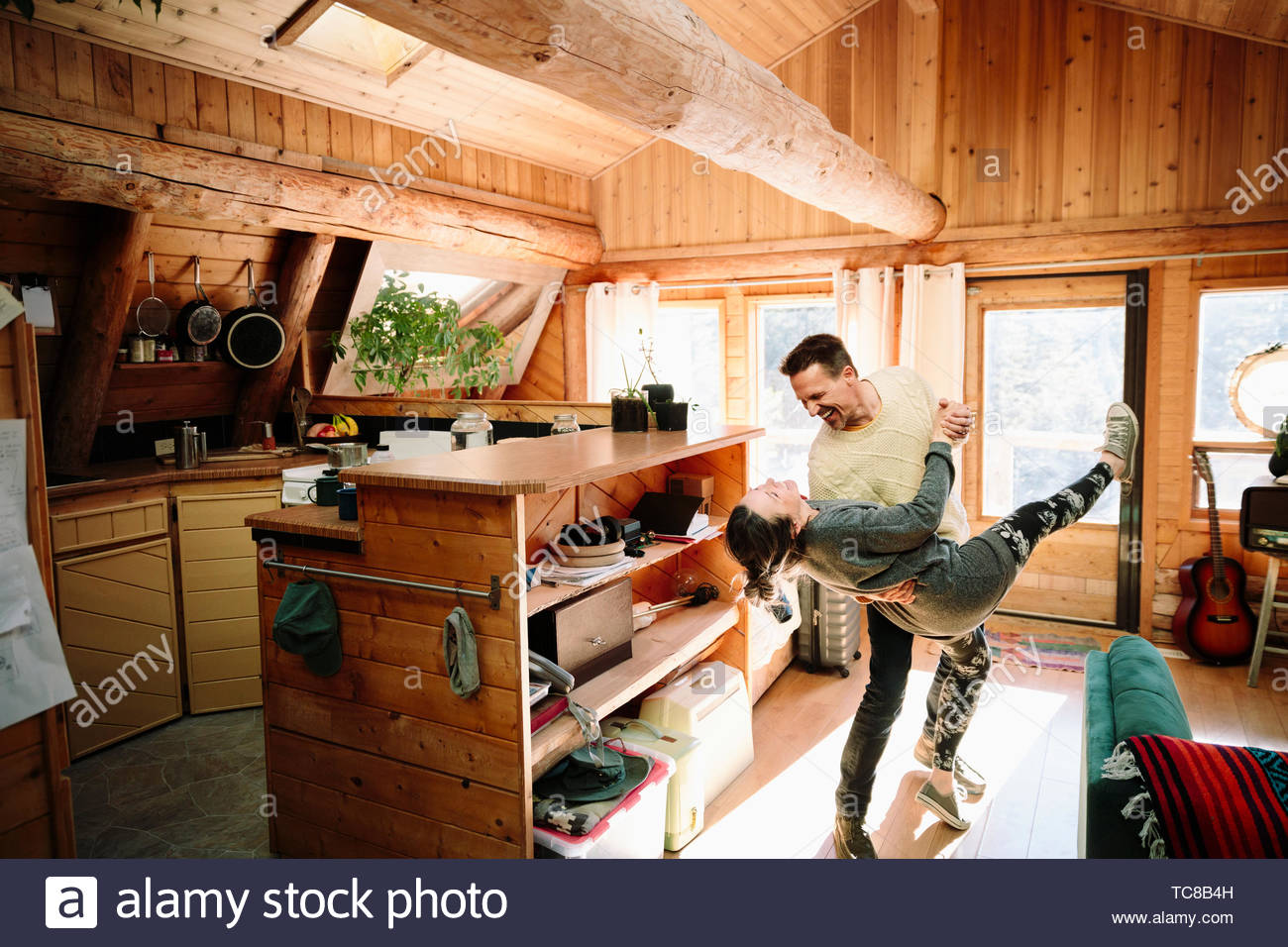Playful couple dancing in cabin Stock Photo