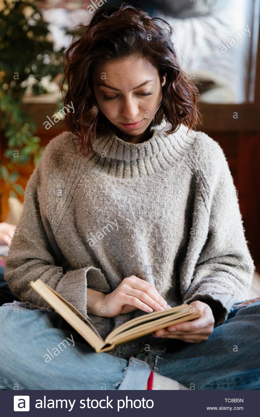 Serene woman reading book - Stock Image