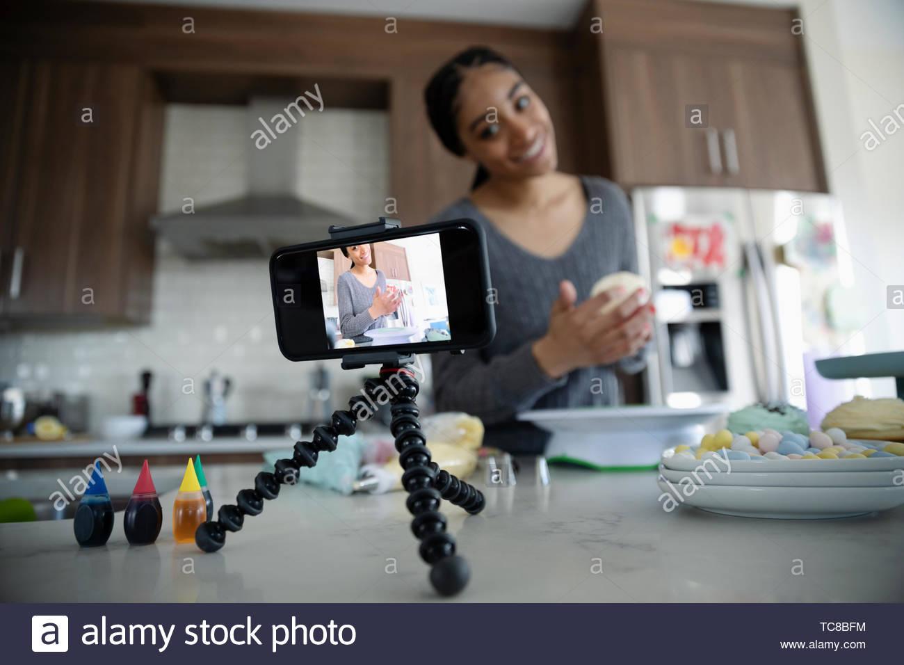 Teenage girl vlogging, decorating cupcakes in kitchen - Stock Image