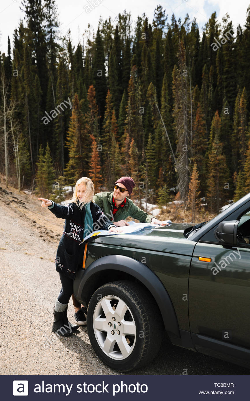 Couple looking at map on hood of SUV at remote roadside Stock Photo