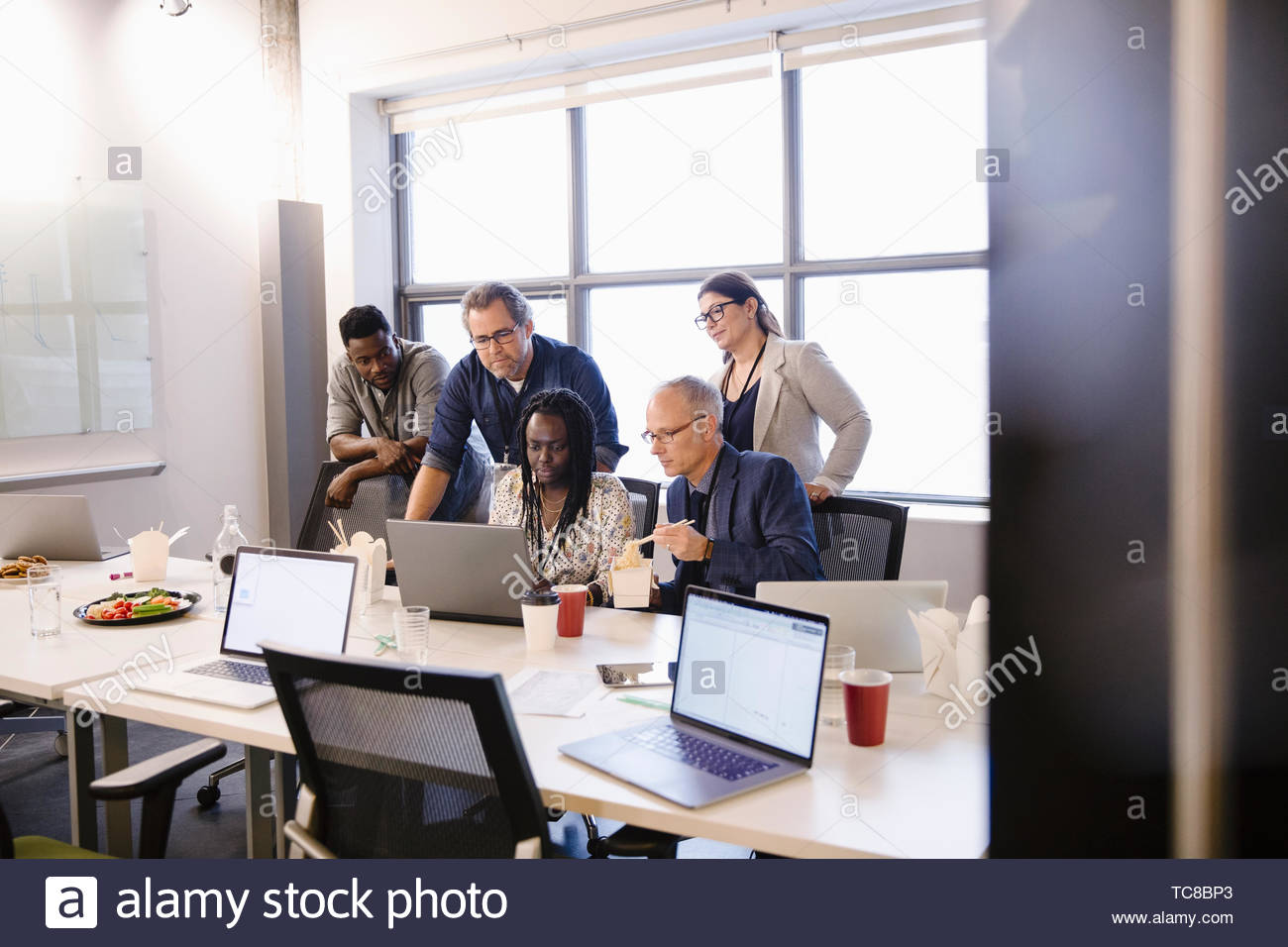Business people working at laptop and eating take out lunch