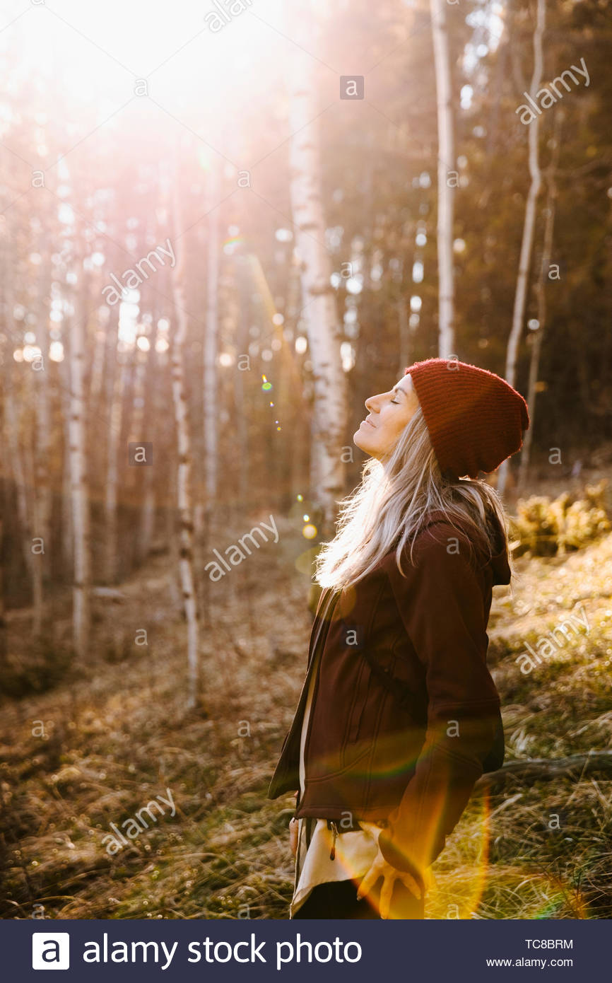 Serene woman basking in sunlight, hiking in woods - Stock Image